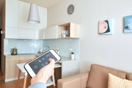 Cropped view of young adult man using app for smart house on modern smartphone with mockup on display, standing in kitchen room