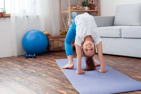 Little girl maintaining healthy lifestyle doing yoga asana chakrasana wheel pose on mat at home looking camera smiling cheerful Stock Photo