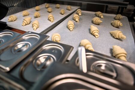 Bakery shop production small business croisssants on silicone mat sheet on tray close-up