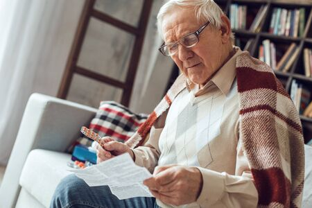 Senior man alone sitting at library sick covered with plaid reading paper with instructions Stock Photo