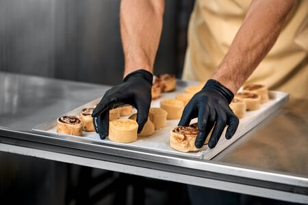 Small Business. Man standing at bakery shop arranging cinnamon rolls on tray close-up