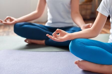 Healthy Lifestyle. Mother and daughter in sportswear sitting on yoga mat in lotus position meditating hands in mudra close-up
