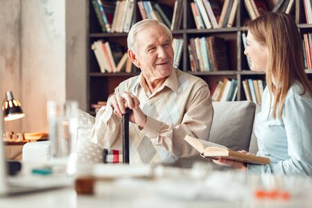 Father and daughter at home library sitting man looking at woman holding book laughing Stock Photo