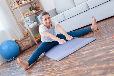 Healthy Lifestyle. Young woman doing yoga at home sitting legs apart bending down stretching smiling joyful