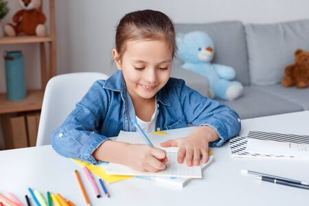 Home Education. Gitl sitting at table drawing using color pencils smiling excited close-up Stock Photo