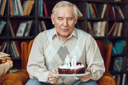 Senior man alone sitting at library holding cake blowing candles concentrated