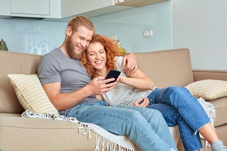 Young adult husband and wife using modern smartphone at home Stock Photo