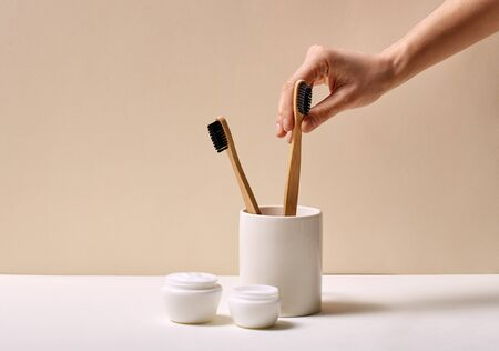 Eco-friendly Concept. Bamboo toothbrushes in cup facial cream soap and towel isolated in bathroom close-up