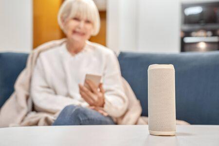 Retirement woman sitting near smart speaker and wireless digital assistant