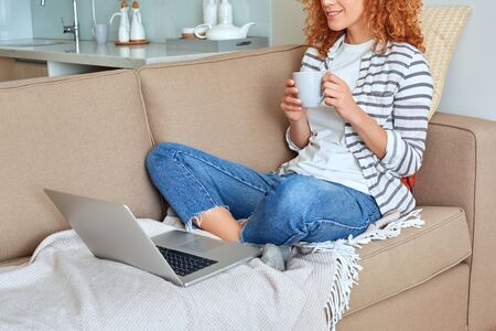 Cropped view of smiling young adult woman spending free time at home, holding beverage in hands, sitting on couch, looking at modern laptop computer