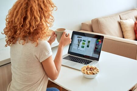 Back view of young adult freelancer girl sitting behind modern laptop computer with beverage in hands, looking at display with graphic design logo Stock Photo