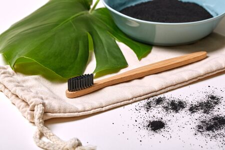 Natural paste, black powder with activated carbon. Flat lay composition with bamboo toothbrush. Modern popular way to clean the mouth. ?aries prevention, bleaching, lightening. Ingredient, absorption. Stock Photo
