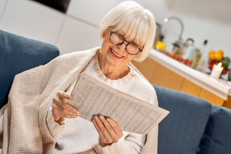 Horizontal house image. 60s 70s old beauty woman at home reads newspaper wearing glasses and cozy plaid. Enjoy good information smile laugh. Happy senior elderly lady. Announcement offline advertising