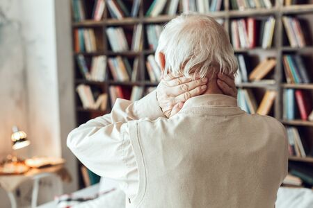 Senior man alone standing at library massaging neck back view close-up