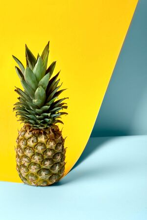 Close up ripe one whole pineapple with green leaves, vertical photo. Flat lay, top view, summer concept. Place for text, copy space. Vertical shot. Creative yellow and blue isolated background, shadow