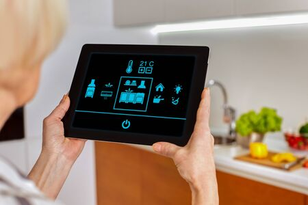 Smart home system kitchen control! Picture from back blurred background old woman hold tablet look on icons monitor device in fonteground. Touch fingers manage temperature room house interior. Mockup