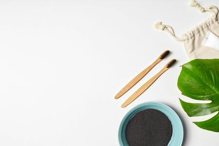 Minimalist photography of oral hygiene products, dental care, gums, tongue. Trendy natural black toothpaste, popular, young people like. Bamboo toothbrush, green leaf, linen pouch and copyspace. White
