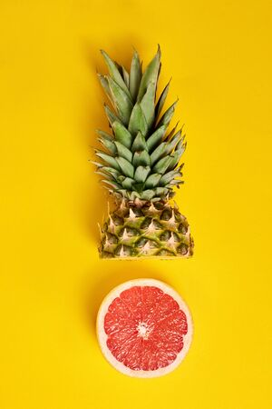 Yellow background with copy space, top view concept, creative composition with healthy fresh half pineapple head and round grapefruit. Organic, natural, ripe fruit on table. Advertising summer layout.