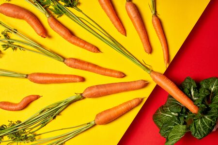 Many fresh orange carrots on isolated colored background laid out rhythmically, pattern on table. Creative look at food composition with copy space top view. Flat lay healthy natural concept. Eco, bio Фото со стока