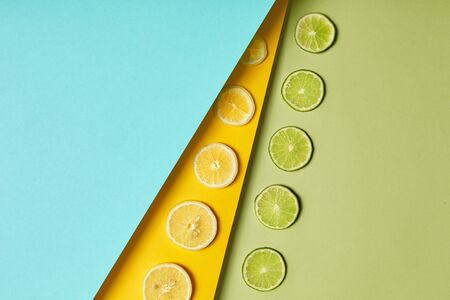 Minimal food healthy flat lay, green lime, yellow lemon slices pattern on colored background. Paper texture, Top view concept with copy space. Fresh ingredients for juice, cocktails or smoothie. Detox
