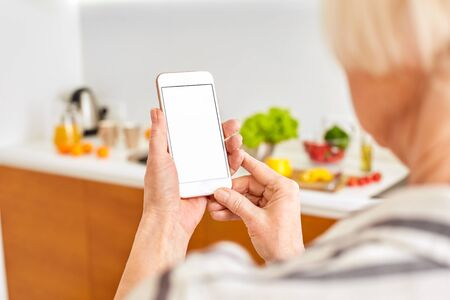 Senior woman at home standing at kitchen holding smartphone controlling smart home system back view close-up mockup copy space for text or product