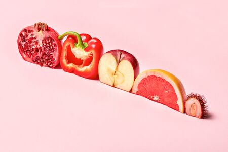 Flat lay of exotic organic asian fruits, horizontal concept. Pink background, copy space, cut in half, line with shadow. Red pomegranate, bell pepper, ripe apple, juicy grapefruit, organic lychee. Bio Фото со стока