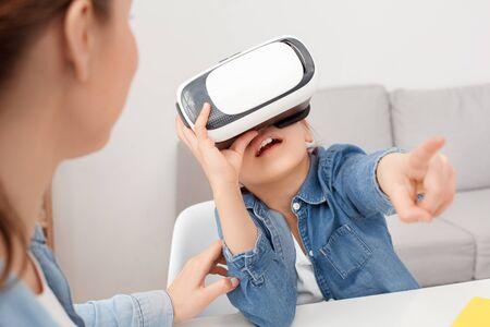 New technology to spent time together with family. Entertainment mother and daughter. Joyful cheerful nice cute two person wearing VR headset playing video games at home. Child girl try to catch touch
