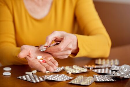 Unhealthy middle aged old woman holding a pill unpacks tablets before use. Close up of senior person sitting at home kitchen table with many packaging of medicines. High temperature concept. Different
