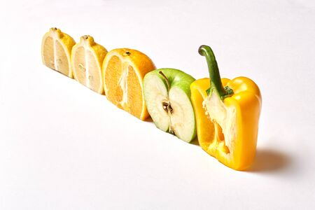 Banner of isolated fresh fruits on white background sliced in half. Cut bell pepper, apple, orange, lemon in a row. Various type of healthy organic vegetable laid on table. Eco, bio