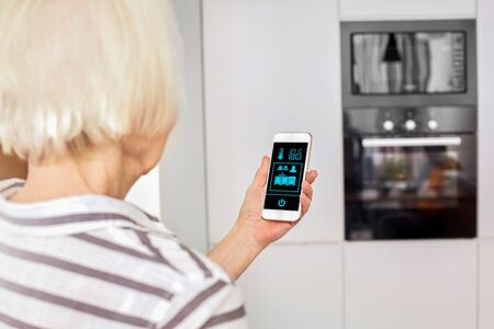 Horizontal concept. Female old hands holding phone with app smart home screen in living room kitchen house. Touch icon manage system. Elderly lady control lights with app. Safety environment Interior
