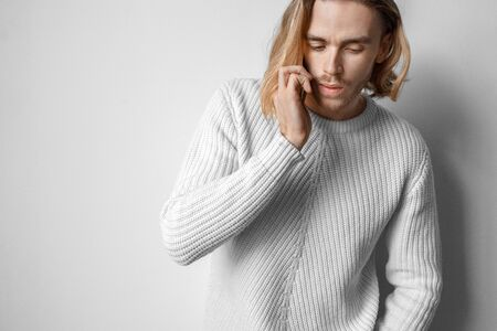 Freestyle. Young man in sweater standing isolated on white talking on smartphone pensive
