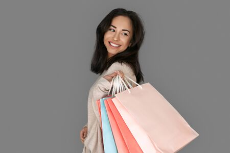Shopping Concept. Woman standing isolated on grey with bags looking aside cheerful