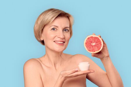 Mature aged model holding natural cream and slice of citrus in hands