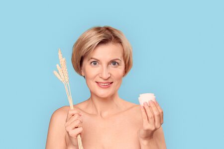 Mature aged female holding herbs and cream in hands Banco de Imagens