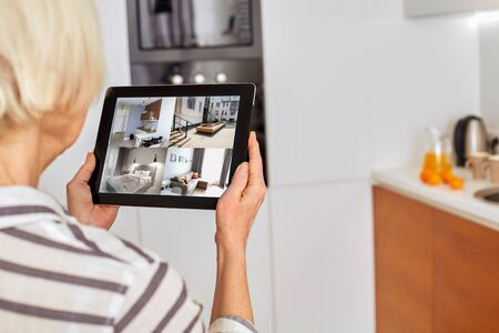 Senior woman at home standing at kitchen holding digital tablet controlling smart home system back view checking cameras close-up