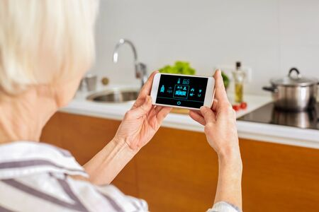 Senior woman at home standing at kitchen holding smartphone controlling smart home system back view close-up turning on light