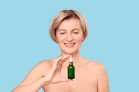 Middle aged female holding organic rejuvenation oil in glass bottle
