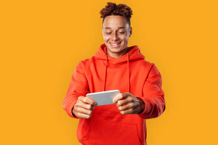 Freestyle. Mulatto freckled guy in hoodie standing isolated on yellow playing game on smartphone smiling cheerful