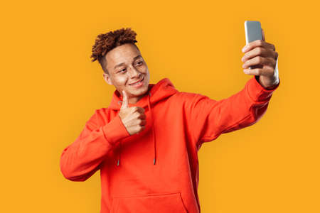 Freestyle. Mulatto freckled guy in hoodie standing isolated on yellow taking selfie photo on smartphone showing thum up smiling joyful
