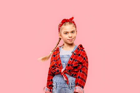 Freestyle. Little girl in bandana on head with braids standing isolated on pink posing smiling confident