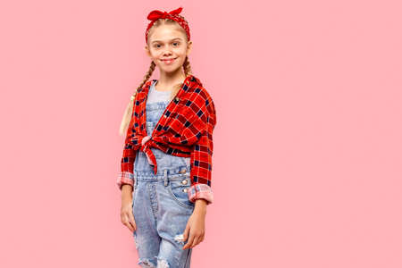 Freestyle. Little girl in bandana on head with braids standing isolated on pink posing to camera happy copy space