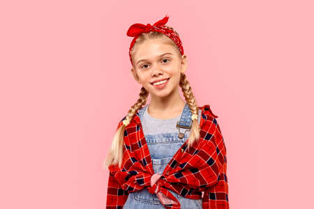Child girl posing against pink background, looking at camera