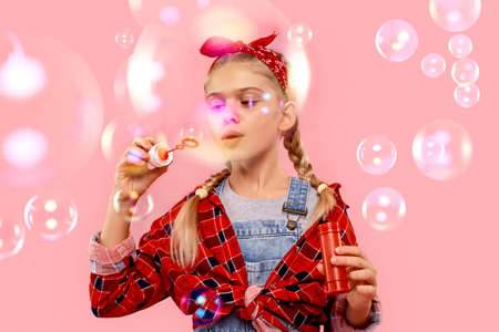 Little girl making soap bubbles, blowing air