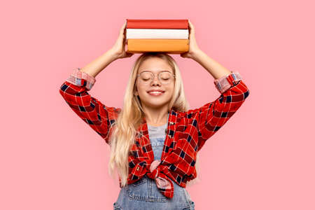 Freestyle. Little girl in eyeglasses standing isolated on pink with books on head closed eyes smiling joyful