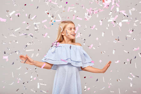 Freestyle. Little girl in dress isolated on gray dancing in flying confetti looking aside smiling surprised