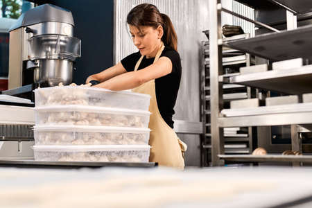 Professional chef unpack raw dough from plastic container