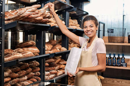 Small Business. Young woman in apron at bakery shop taking baguette from shelf putting into paper bag looking camera happy