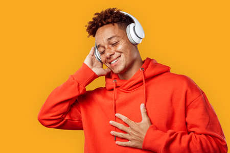 Freestyle. Mulatto freckled guy in hoodie and headphones standing isolated on yellow listening music smiling delightful