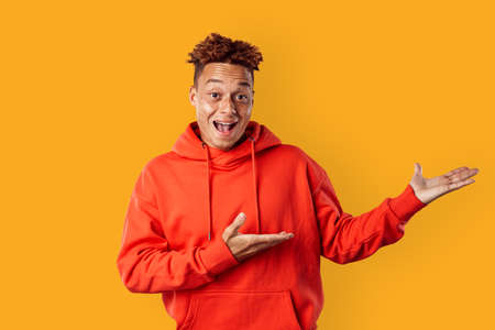 Freestyle. Mulatto freckled guy in hoodie standing isolated on yellow showing copy space smiling excited