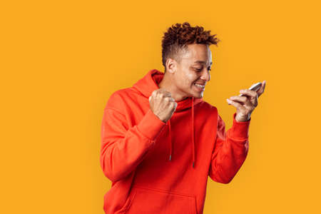Freestyle. Mulatto freckled guy in hoodie standing isolated on yellow browsing news on smartphone hand in fist smiling happy Stock fotó